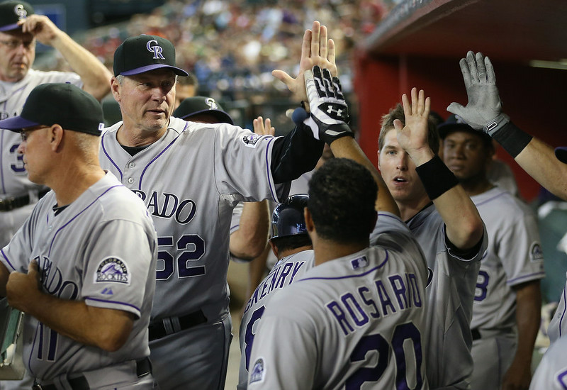 . Pitching coach Jim Wright #52 of the Colorado Rockies congratulates Wilin Rosario #20 after Rosario hit a solo home-run against the Arizona Diamondbacks during the sixth inning of the MLB game at Chase Field on August 10, 2014 in Phoenix, Arizona.  (Photo by Christian Petersen/Getty Images)