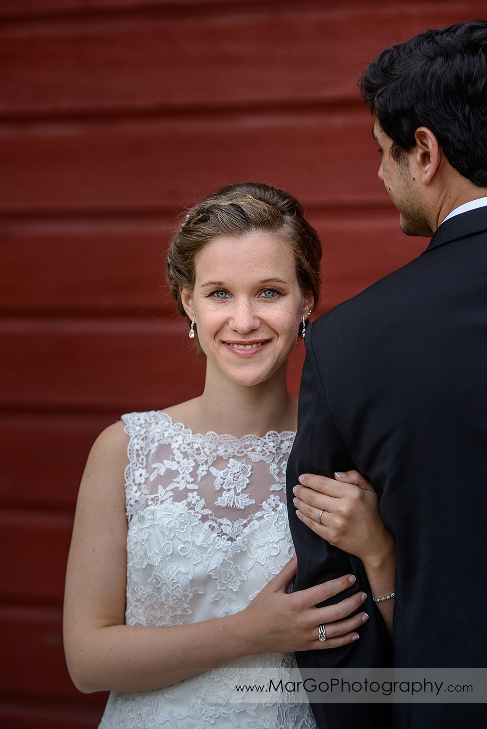 portrait of bride holding hands on groom's arm on the red barn wall during bridal session at Shinn Historical Park and Arboretum in Fremont