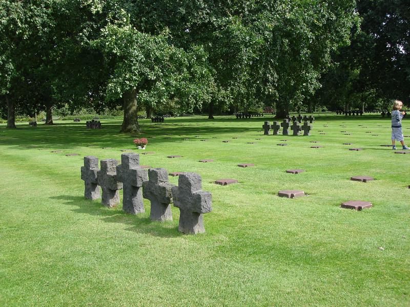 """Hier bevinden zich 21.500 graven. Hier staan kleine groepjes van zwarte kruisen verspreid. Dit symboliseerd voor de Duitser """"kameraadschap in de dood""""."""