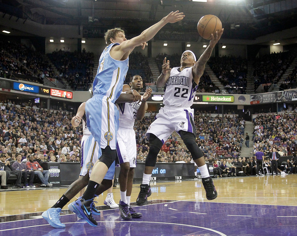 . Sacramento Kings guard Isaiah Thomas, right, drives to the basket against Denver Nuggets center Timofey Mozgov, left, of Russia, during the third quarter of an NBA basketball game in Sacramento, Calif., Sunday, Jan. 26, 2014. The Nuggets won 125-117.(AP Photo/Rich Pedroncelli)