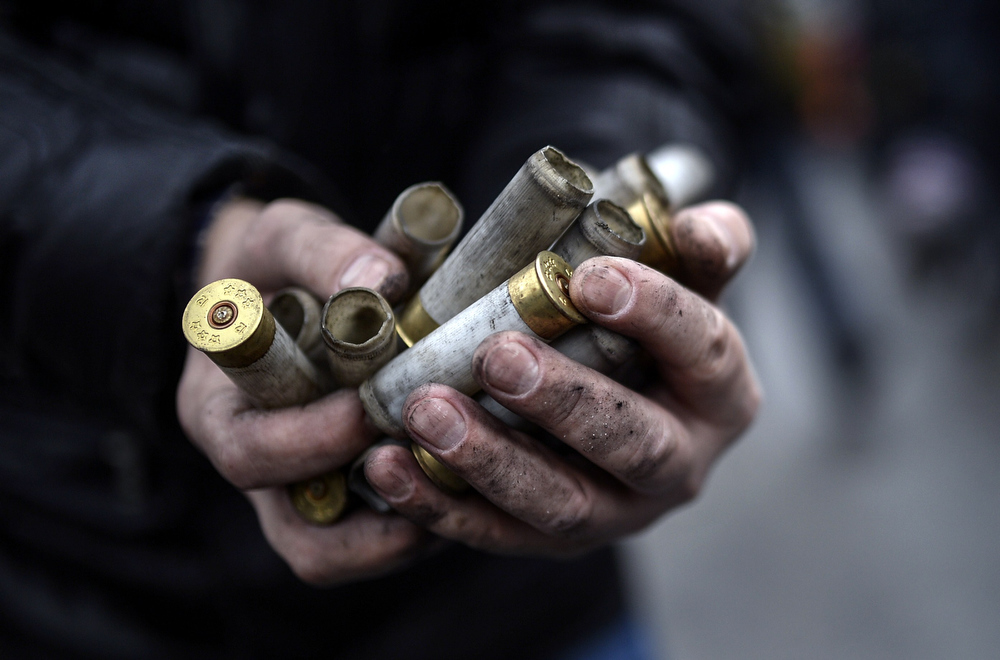 Description of . An anti-government protester shows empty bullet casings used by riot police against demonstrators in central Kiev on February 20, 2014. At least 25 protesters were killed on February 20 in fresh clashes between thousands of demonstrators and heavily-armed riot police in the heart of Kiev, AFP correspondents at the scene said. The bodies of eight demonstrators were lying outside Kiev's main post office on Independence Square, an AFP reporter said. The bodies of 17 other demonstrators with apparent gunshot wounds were also seen in the vicinity of two hotels on opposite sides of the protest encampment. AFP PHOTO/ SERGEI SUPINSKYBULENT KILIC/AFP/Getty Images