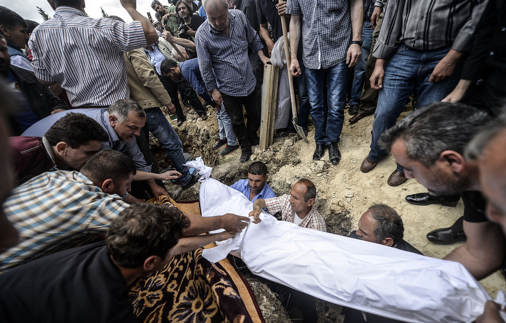 . People hold the body of a miner during a funeral ceremony on May 15, 2014, in the western town of Soma in the Manisa province. Turkey\'s four biggest unions will hold a one-day protest strike  as anger over the country\'s worst mining accident mounts, with 282 workers confirmed dead and scores still trapped underground.  AFP PHOTO/BULENT  KILIC/AFP/Getty Images
