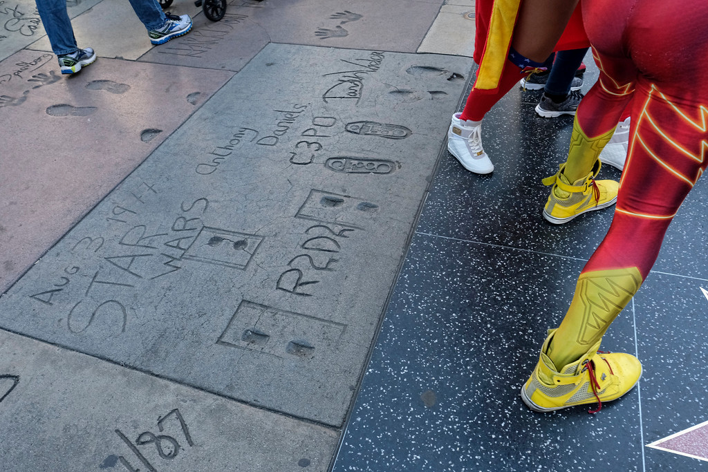 ". Tourists walk past the hand and foot prints for some of the characters from the Star Wars movie in front of the TCL Chinese Theatre along Hollywood Boulevard in Los Angeles on Tuesday, Dec. 27, 2016. Carrie Fisher, who played Princess Leia in the ""Star Wars\"" movies, died Tuesday. She was 60. (AP Photo/Richard Vogel)"