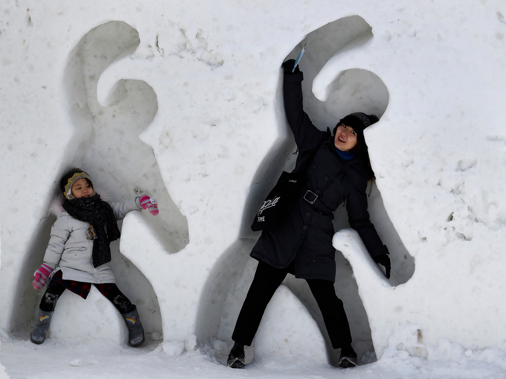. People pose in cutouts in ice built as part of the celebration for the 2018 Winter Olympics at the Pyeongchang Olympic Plaza in Pyeongchang, South Korea, Sunday, Feb. 11, 2018. (AP Photo/Charlie Riedel)