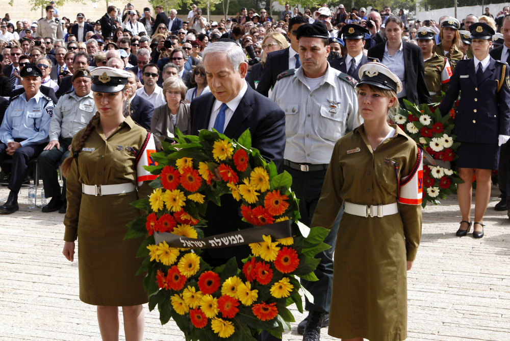 Description of . Israeli Prime Minister Benjamin Netanyahu (C) lays a wreath during the annual ceremony for Holocaust Remembrance Day at the Yad Vashem memorial on April 8, 2013 in Jerusalem, Israel. Across the world, people commemorated the six million Jews murdered by the Nazi regime during World War II between 1933 and 1945. U.S. Secretary of State John Kerry\'s visit is in an attempt to restart mideast peace talks between Israeli and Palestinian officials.  (Photo by Gali Tibbon-Pool/Getty Images)