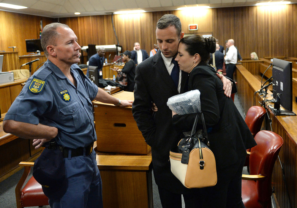 . Oscar Pistorius, hugs his sister Aimee, right, inside court at the end of the second day of his trial at the high court in Pretoria, South Africa, Tuesday, March 4, 2014. Pistorius is charged with murder for the shooting death of his girlfriend, Reeva Steenkamp, on Valentines Day in 2013. (AP Photo/Antoine de Ras, Pool)