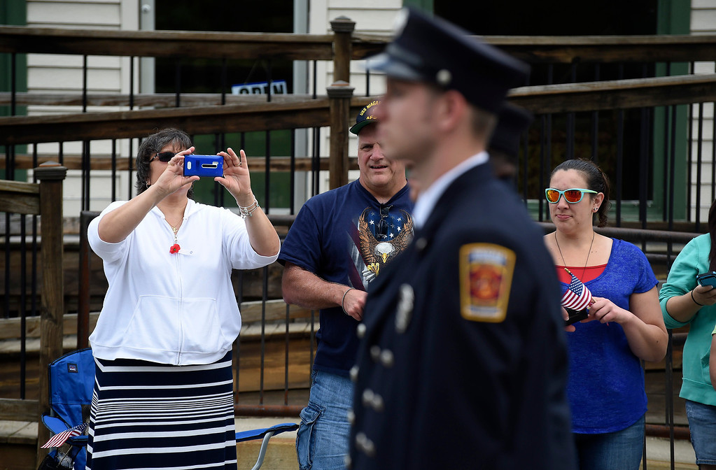 . Kayla Rice/Reformer A woman takes a picture with her phone of the firefighters from the Hinsdale Fire Dept. walking in the Hinsdale Memorial Day parade on Monday morning.