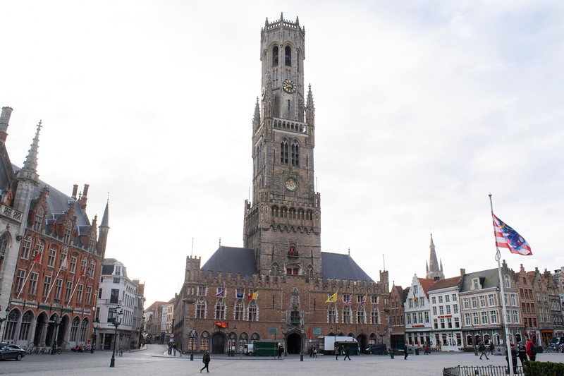 a large gothic belfry in the moiddle of a city street