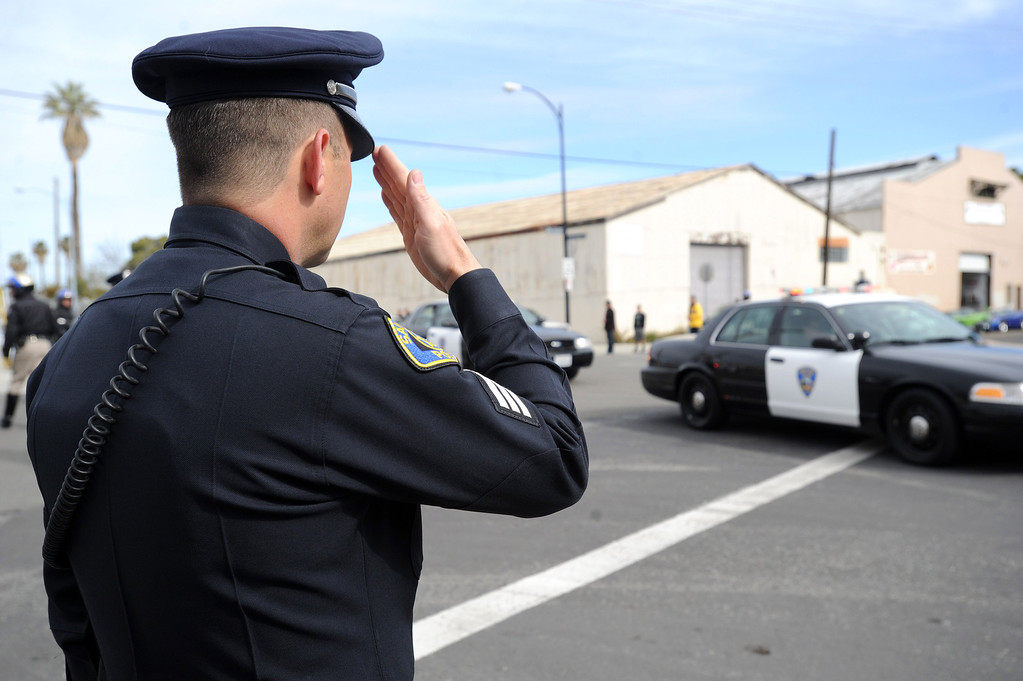 ". San Jose police Sgt. Brian Shab salutes as the Santa Cruz procession arrives at the HP Pavilion in San Jose, Calif. on Thursday, March 7, 2013. Thousands are expected at the pavilion to mourn the loss of the 2 Santa Cruz police officers Loran ""Butch\"" Baker and Elizabeth Butler who lost their their lives in the line of duty on Feb. 26. (Dan Honda/Staff)"