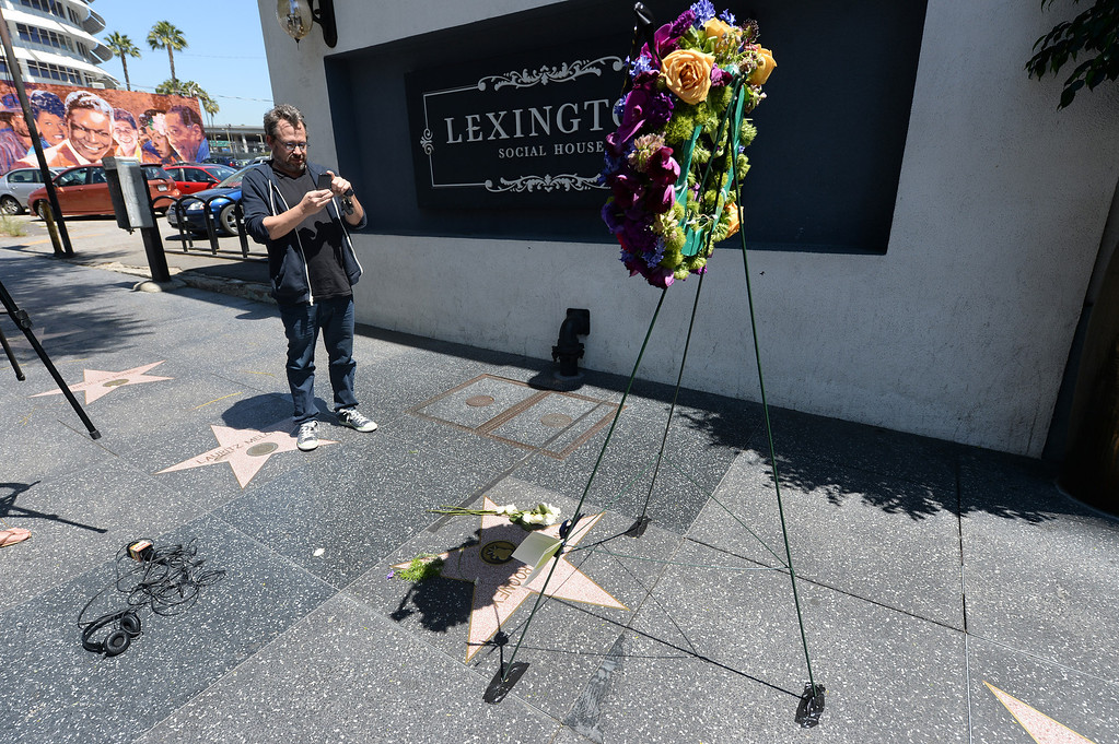 . David Syner, Hollywood, takes a photo of Mickey Rooney�s star on the Hollywood Walk of Fame Monday, April 7, 2014. Flowers were placed on the star located at 1718 Vine Street to honor the actor who died Sunday at the age of 93. (Photo by Hans Gutknecht/Los Angeles Daily News)