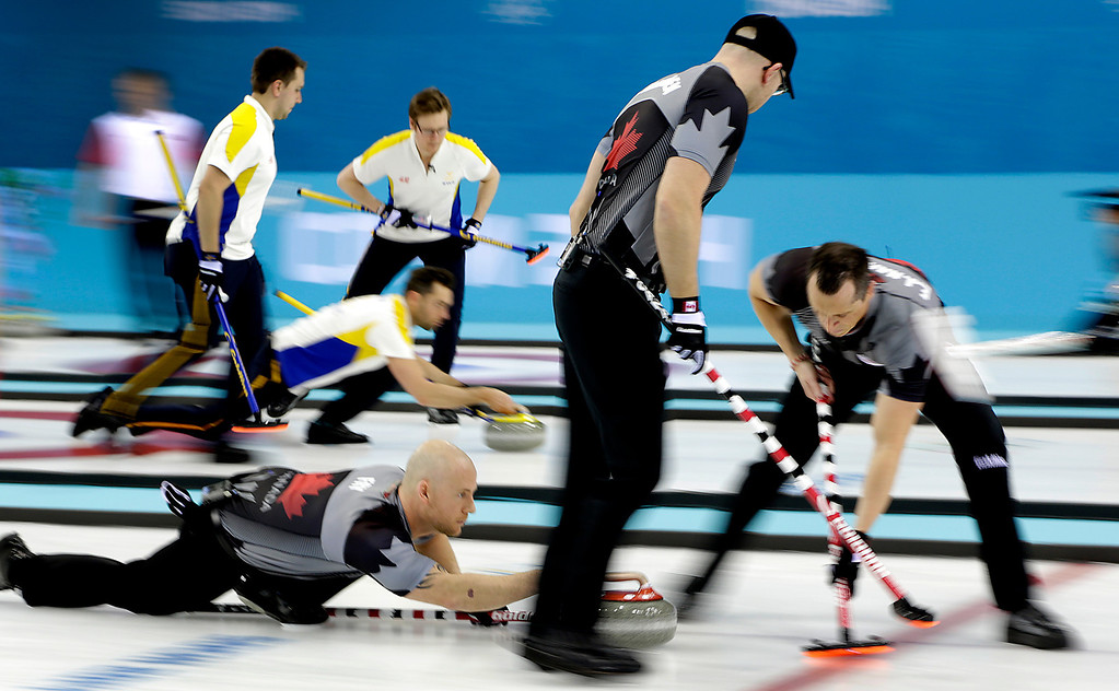 . Canada\'s Ryan Fry delivers the rock while E.J. Harnden, right, and Ryan Harnden, center, sweeps the ice during the men\'s curling competition against Denmark at the 2014 Winter Olympics, Thursday, Feb. 13, 2014, in Sochi, Russia. (AP Photo/Wong Maye-E)