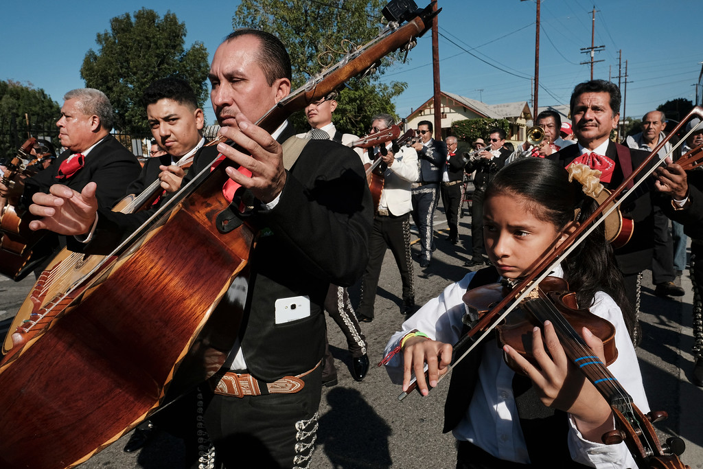 . Mariachis play in the street during the Santa Cecilia procession in the Boyle Heights section of Los Angeles on Tuesday, Nov. 22, 2016. Musicians from around the country gathered for Mariachi Sol de Mexico to celebrate Santa Cecilia. The festival honors Santa Cecilia, the patron saint of musicians. (AP Photo/Richard Vogel)