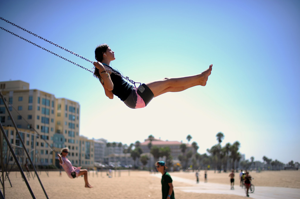 . Maya Sokolow, 16-years-old, enjoys mild temperatures while swinging at the Santa Monica Boardwalk in Santa Monica Thursday, September 5, 2013. (Photo by Hans Gutknecht/Los Angeles Daily News)