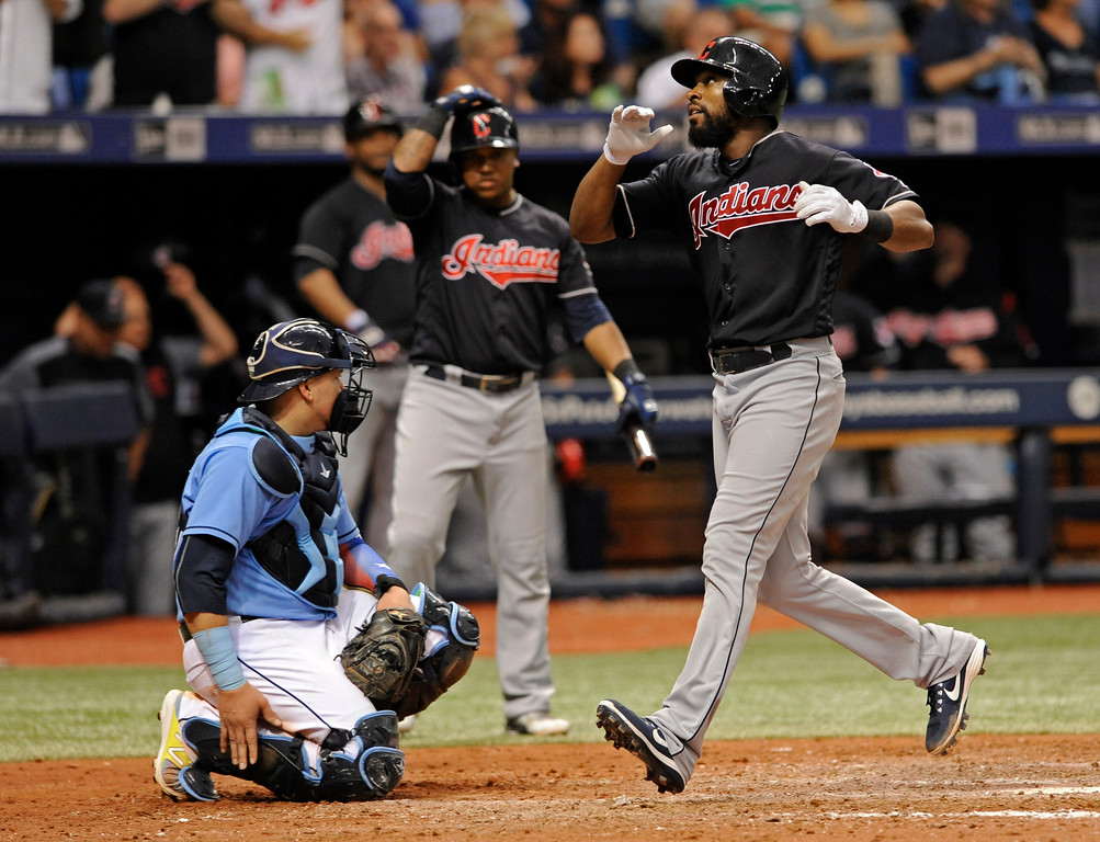 . Cleveland Indians on-deck batter Jose Ramirez, center, watches as Austin Jackson runs by Tampa Bay Rays catcher Jesus Sucre, left, after Jackson hit a solo home run off Tampa Bay reliever Tommy Hunter during the eighth inning of a baseball game Sunday, Aug. 13, 2017, in St. Petersburg, Fla. (AP Photo/Steve Nesius)