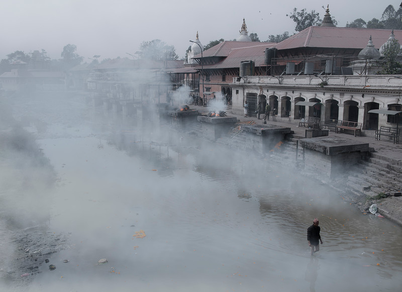 Morning mist covers the holy Bagmati river, whist burning pyres send soles into mukti.  Pashupatinath, Nepal, 2019.