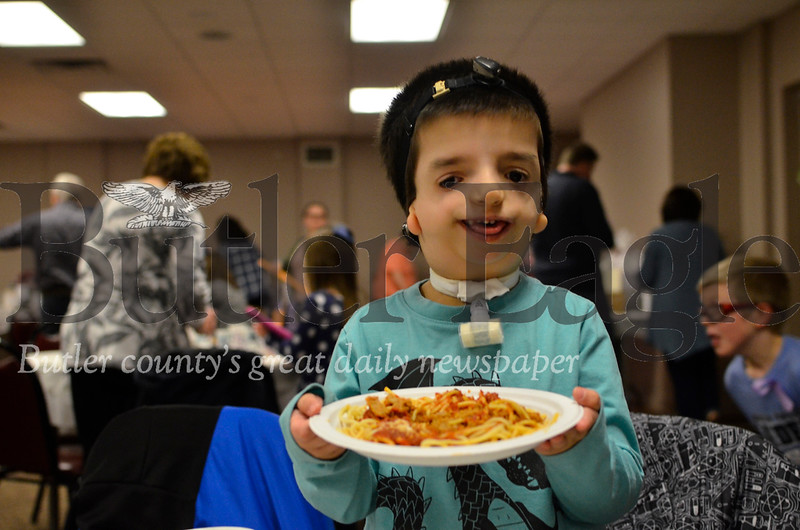 Asher Kearns, 6, holds up a plate of spaghetti at a luncheon in Cranberry Township Saturday. Kearns has Treacher Collins syndrome and is a first grade student at the Western Pennsylvania School for the Deaf. Tanner Cole/Butler Eagle