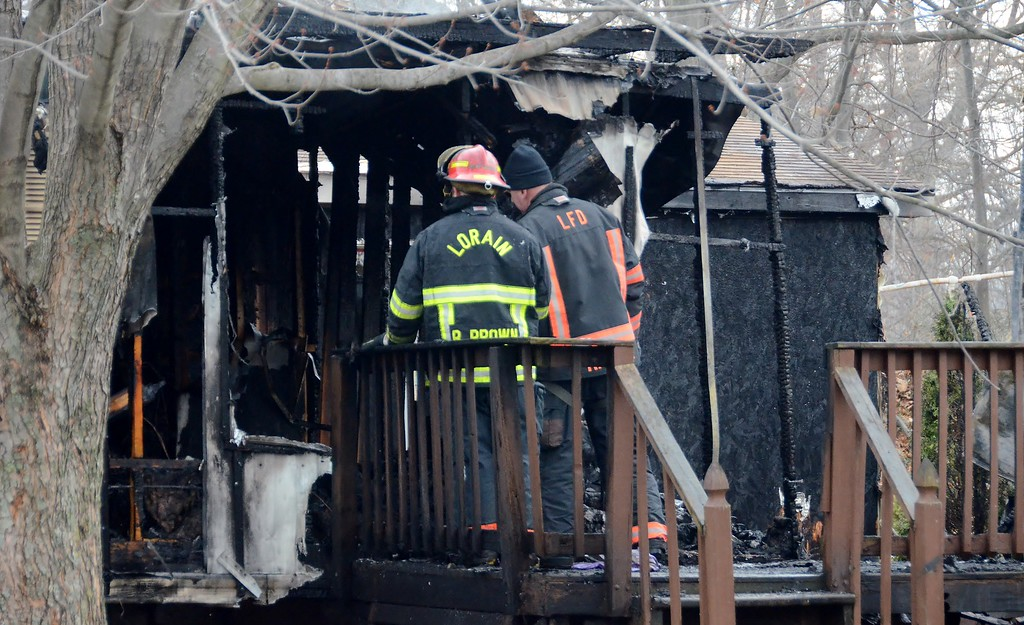. Lorain firefighters continue overhaul at a mobile home in the 39000 block of Reid Avenue on Dec. 23 after an early morning fire claimed the life of a 9-year-old and injured one other person. (Kelsey Leyva � The Morning Journal)