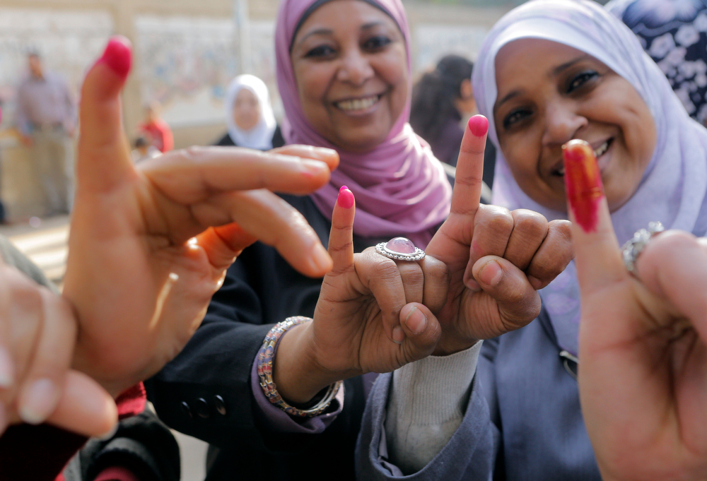 . Egyptians women show their inked fingers after casting their votes at a polling station in Cairo, Egypt, Tuesday, Jan. 14, 2014. Egyptians are voting on a draft for their country\'s new constitution that represents a key milestone in a military-backed roadmap put in place after President Mohammed Morsi was overthrown in a popularly backed coup last July. (AP Photo/Amr Nabil)