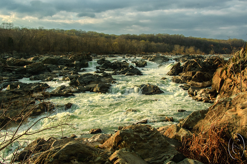 18 Apr 16With today being national theft day, I thought a shot of some rapids might be appropriate as a representation of what is happening to our hard earned capital. And these rapids happen to be not far from out national capitol on the Potomac River separating MD and VA. They were not far from where Jan taught 2nd grade during our 8 year stay and we made many a visit to both sides of the falls as the view from each side is quite different. For those of you on the left coast this should be a must see when visiting the DC area; for those of you on the right coast, if you haven't yet visited, this might be a good time to so do. IF my memory serves me correctly, rapids are graded from zero difficulty to seven, and the rapids here at Great Falls garner a true 7! There is a LARGE display sign on the MD side discussing the rapids a with a STRONG warning about the associated undertow which is responsible for several deaths annually, in part it is implied because people don't pay attention to warnings such as that sign. I first began to gain an appreciation for Great Blue Herons at these two parks, even though I had seen plenty of them here in the greater Puget Sound area years earlier. I just never paid them any attention at that time. Here I got to watch them fishing at the edges of these rapids working in waters I would never consider getting near, but then, in case of trouble, they could fly and I can't. I thought I had shared a couple of shots of the birds working the rocky edges for a meal earlier but in looking through the archives I can't find what I thought I had shared, so perhaps a bit later I'll work up a couple shots that illustrate my comments about the birds. Meanwhile here is a shot of the waters in which the birds are frequently seen looking for a meal.  The base image was given a little micro contrast enhancement and that was it.  Nikon D70; 24 - 124; Aperture Priority;  ISO 200; 1/ 320 sec @ f / 8 .