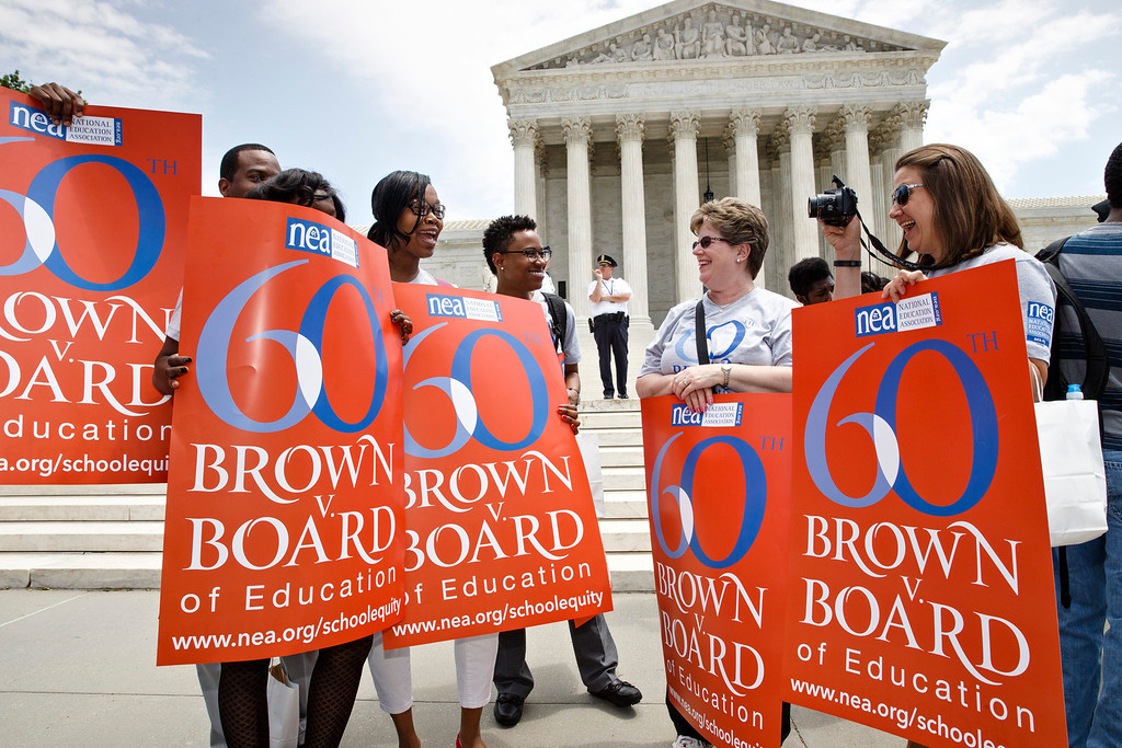 . This photo taken May 13, 2014 shows National Education Association staff members from Washington joining students, parents and educators at a rally at the Supreme Court in Washington on the 60th anniversary Brown v. Board of Education decision that struck down ìseparate but equalî laws that kept schools segregated. Saturday marks the 60th anniversary of the landmark Brown v. Board of Education decision. Many inequities in education still exist for black students and for Hispanics, a population that has grown exponentially since the 1954 ruling. (AP Photo)
