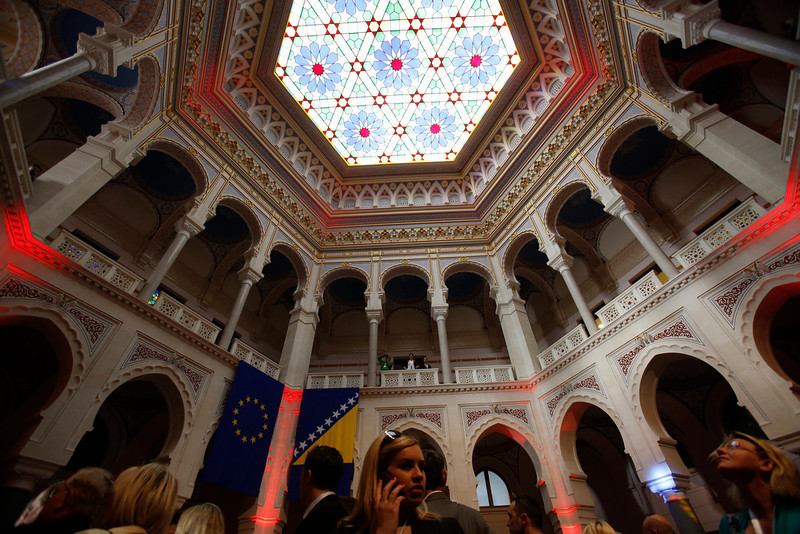 . FILE - In this Friday, May 9, 2014 file photo, visitors look at decorations in the newly re-opened National Library in the Bosnian capital of Sarajevo. Sarajevo re-opened its reconstructed National Library building 22 years after the city landmark was destroyed during the Bosnian war along with its almost 2 million books and manuscripts. The re-opening comes in time for the June ceremonies that will mark the Centenary of the beginning of World War I. (AP Photo/Amel Emric, File)