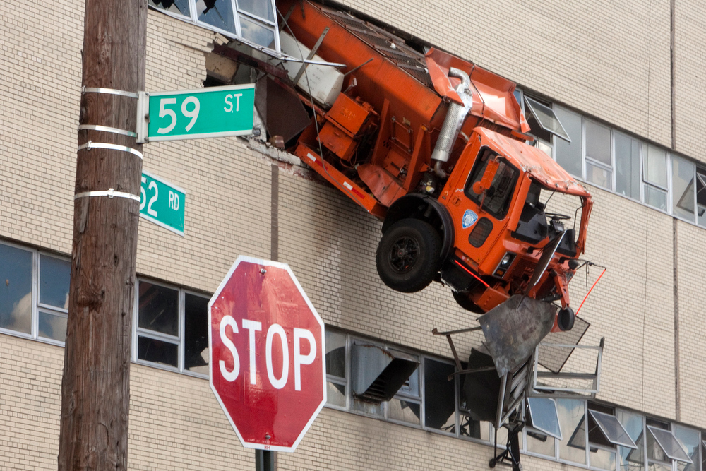 Description of . A 15-ton salt-spreading truck hangs through the wall of a Sanitation Department building in in the Queens borough of New York, Aug. 17, 2011. The truck burst through the wall of a the sprawling sanitation repair depot on Wednesday morning and hung 30 feet above the ground until rescuers could free its driver, who was hospitalized with injuries but listed in stable condition, authorities said. (Dave Sanders/The New York Times)