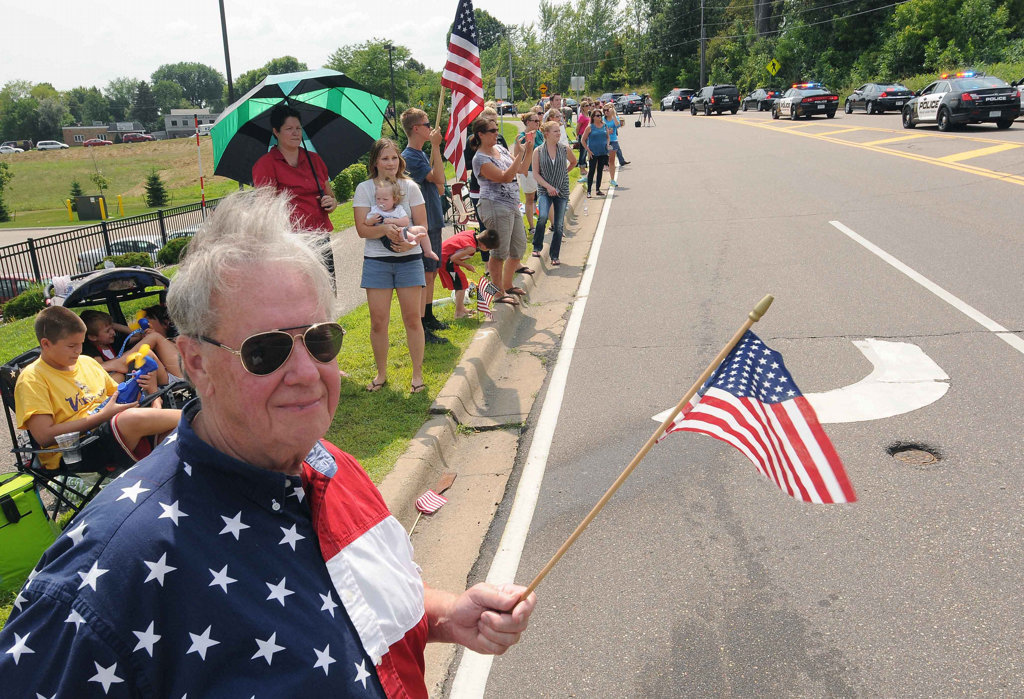 . John Bergstrand of Annandale, Minn. wears his red, white & blue shirt, which he always wears on the Fourth of July, as a long line of police cars stream down Dodd Road, on their way to the burial service for officer Scott Patrick at Acacia Park Cemetery.  (Pioneer Press: Scott Takushi)
