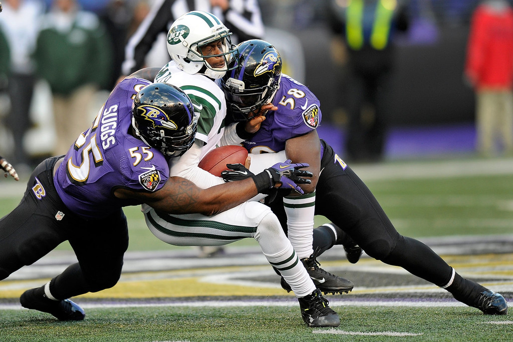 . New York Jets quarterback Geno Smith, center, is tackled by Baltimore Ravens outside linebacker Terrell Suggs, left, and outside linebacker Elvis Dumervil, right, during the second half of an NFL football game in Baltimore, Sunday, Nov. 24, 2013. The Ravens won 19-3. (AP Photo/Nick Wass)