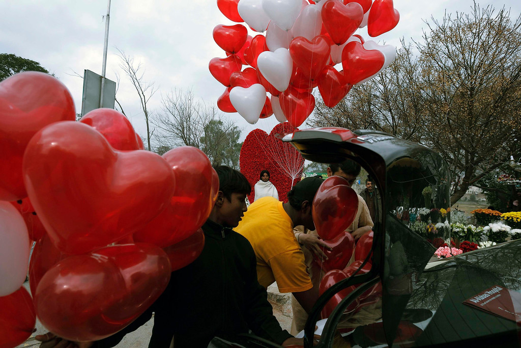 . Men try to fit heart-shaped balloons in the trunk of a car on Valentine\'s Day in Islamabad February 14, 2013. REUTERS/Zohra Bensemra