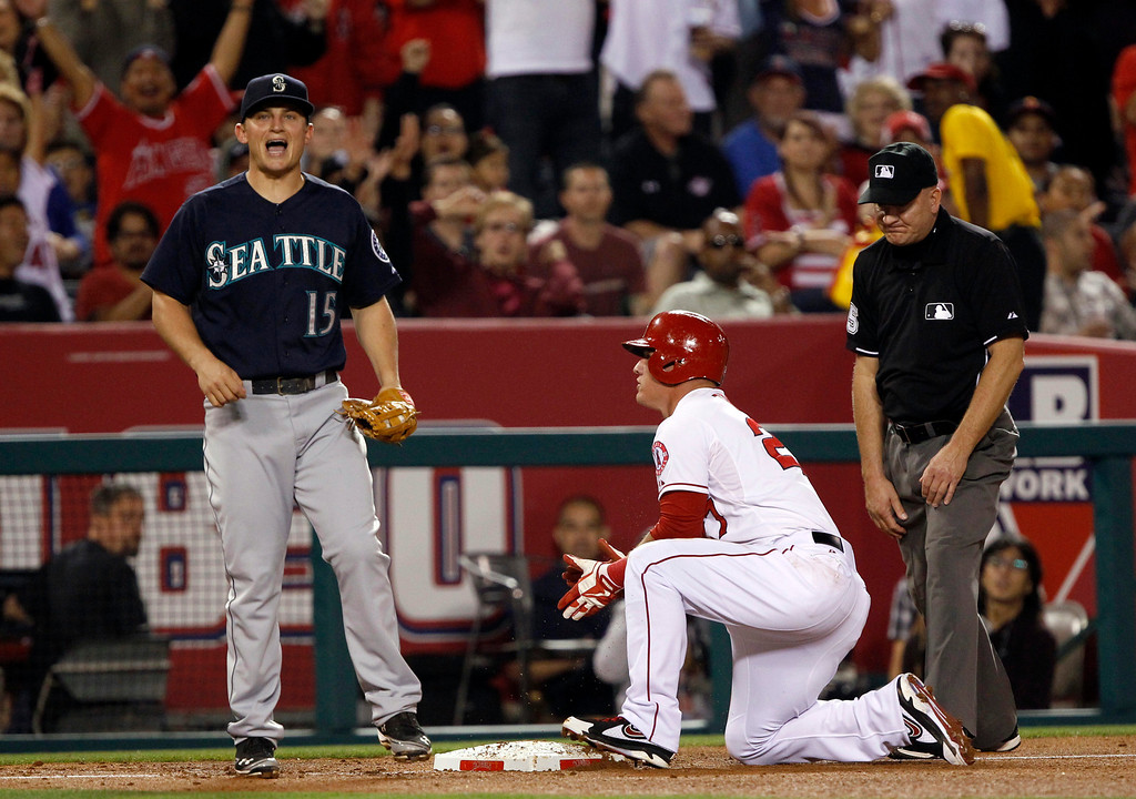. Seattle Mariners third baseman Kyle Seager (15) lets out a scream after third base umpire Gerry Davis, right, called Los Angeles Angels\' Mike Trout, center, safe after a tag, for a triple, in the fourth inning during a baseball game Tuesday, May 21, 2013 in Anaheim.    (AP Photo/Alex Gallardo)