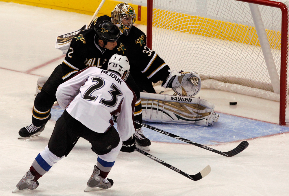 . Colorado Avalanche right wing Milan Hejduk (23) scores a goal against Dallas Stars goalie Kari Lehtonen (32) and  defenseman Nicklas Grossman (2) during the first period of a NHL hockey game in Dallas,  Saturday, Nov. 20, 2010. (AP Photo/LM Otero)