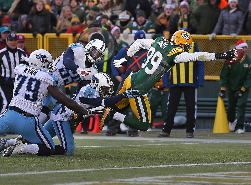 . James Jones #89 of the Green Bay Packers reaches over the goal line to score as he is hit by Jarius Wynn #79, Zach Brown #55 and Alterraun Verner #20 of the Tennessee Titans at Lambeau Field on December 23, 2012 in Green Bay, Wisconsin. The Packers defeated the Titans 55-7. (Photo by Jonathan Daniel/Getty Images)