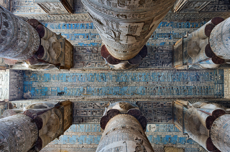[EGYPT 29539] 'Recently restored Astronomical Ceiling in Hathor Temple at Dendera.'  Looking up in the outer hypostyle hall of the Hathor Temple at Dendera gives you a dazzling view of the astronomical ceiling, that was restored between 2006 and 2011. It is a mysterious world inhabited by star gods and zodiac  signs but also by weirder creatures such as snakes on tall legs and birds with human heads.  The astronomical ceiling consists in total of seven separate strips, which are conspicuous by their bright blue colour, that was invisible under a layer of soot before the restoration. Here we see the three strips east from centre.   The Second Strip East from centre we see in its entirety in this picture. It consists of a lower and upper register. The lower register is in its right-hand part inhabited by the goddesses of the twelve hours of the day and their associated deities. In the middle and left-hand part of the register the sun, moon, Sirius, Orion and Venus are sailing across the sky in their boats.  The upper register begins and ends with a representation of one of the four winds. On the left are two boats carrying Isis, Osiris, Ra and Harsomptus. The rest is filled with personifications of decanal stars. The decans of Egyptian astronomy were 36 stars or star groups near the ecliptic  whose rise or transit could be used to tell the time during the night. Eventually they were also used by astronomers as place-markers in the sky to divide up the Ecliptic in equal portions. Decans first appear during the Middle Kingdom on the inside of coffin lids, providing the deceased with his own private start clock. Unfortunately, during the subsequent centuries many different lists of decanal stars were developed and very few of these stars can be identified on a modern star map. The decans in this register were listed by Neugebauer and Parker as stars 1, 2 and 21 till 36 of the Seti I B decan family. Stars 3 till 20 can be found on the second strip west from centre (see pictures 29572 and 29573.)  For an overview of the entire astronomical ceiling see picture 29525. This part of the Dendera Temple was built during the Roman period (first century AD). Photo Mick Palarczyk.