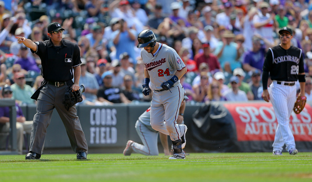 . Trevor Plouffe #24 of the Minnesota Twins is ordered to take home plate by home plate umpire Mark Ripperger after a triple and a throwing error as Nolan Arenado #28 of the Colorado Rockies looks on during the fifth inning. (Photo by Justin Edmonds/Getty Images)