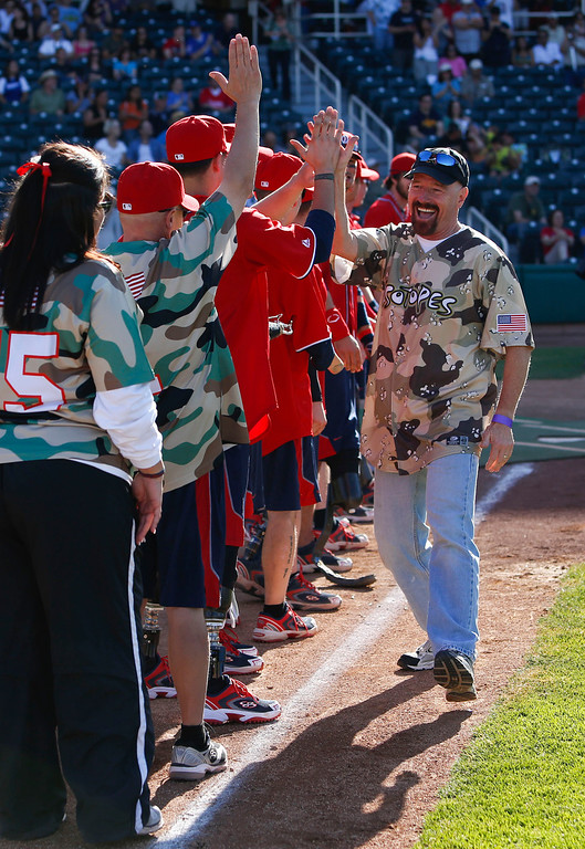 . Emmy Award-winning actor Bryan Cranston, right, high-fives members of the Wounded Warrior Amputee Softball team before a celebrity softball game against the Wounded Warrior team in Albuquerque, N.M., Saturday, May 19, 2012. (AP Photo/Jake Schoellkopf)