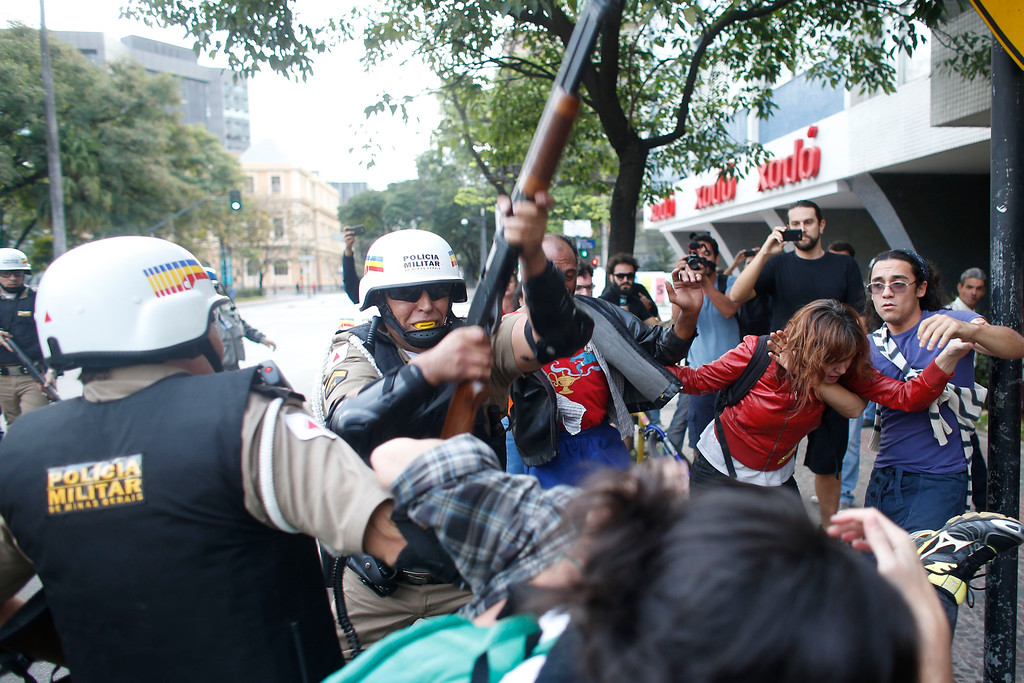 . A policeman hits demonstrators with a shotgun during a protest against the 2014 World Cup in Belo Horizonte, Brazil, Thursday, June, 12, 2014.  (AP Photo/Victor R. Caivano)
