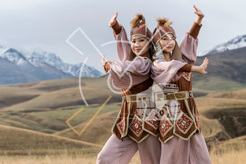 Young Kyrgyz women from Kyrgyzstan dressed up in traditional outfit performing a dance move near to Bishkek,