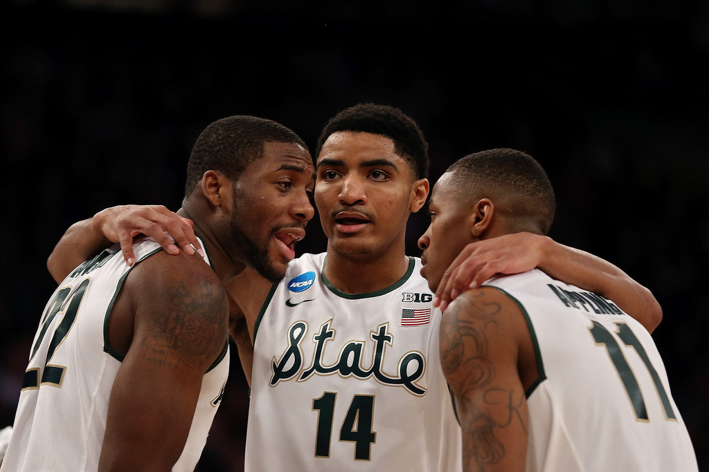 . Branden Dawson #22, Gary Harris #14 and Keith Appling #11 of the Michigan State Spartans talk against the Connecticut Huskies during the East Regional Final of the 2014 NCAA Men\'s Basketball Tournament at Madison Square Garden on March 30, 2014 in New York City.  (Photo by Bruce Bennett/Getty Images)