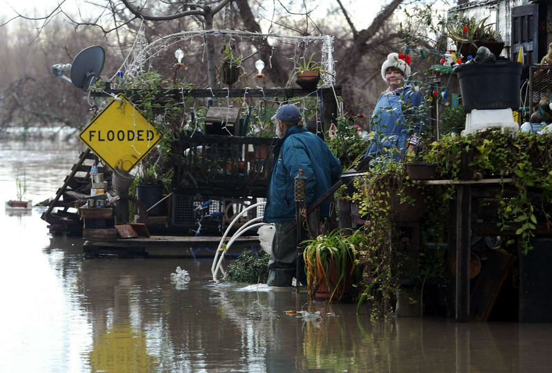 Jackson Davis (left) and Terri Smith (right) stands outside their mobile home where a flooded sign is displayed on the porch along River Rd. near Scotty's landing where the water has risen to the flood line Saturday. - halley photo 12/31/05