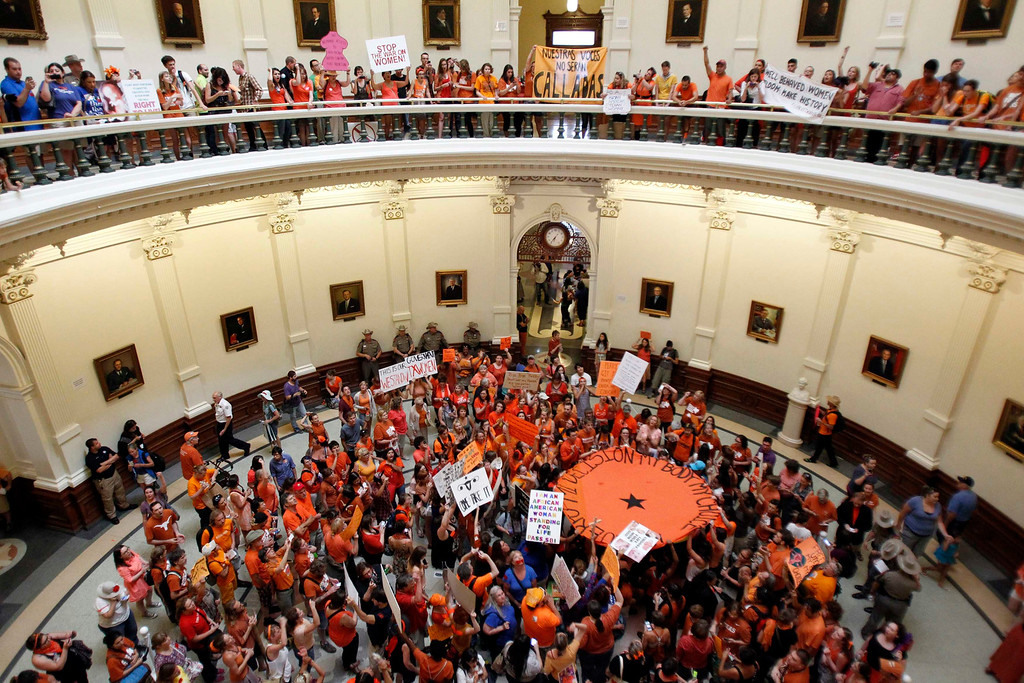 . Abortion rights (in orange) and anti-abortion advocates (in blue) rally in the rotunda of the State Capitol, as the state Senate meets to consider legislation restricting abortion rights in Austin, Texas July 12, 2013. The Republican proposal that would ban most abortions in Texas after 20 weeks of pregnancy moved toward a possible final vote in the state Senate Friday, and Democrats fiercely opposed to the measure conceded they will not be able to stop it.   REUTERS/Mike Stone
