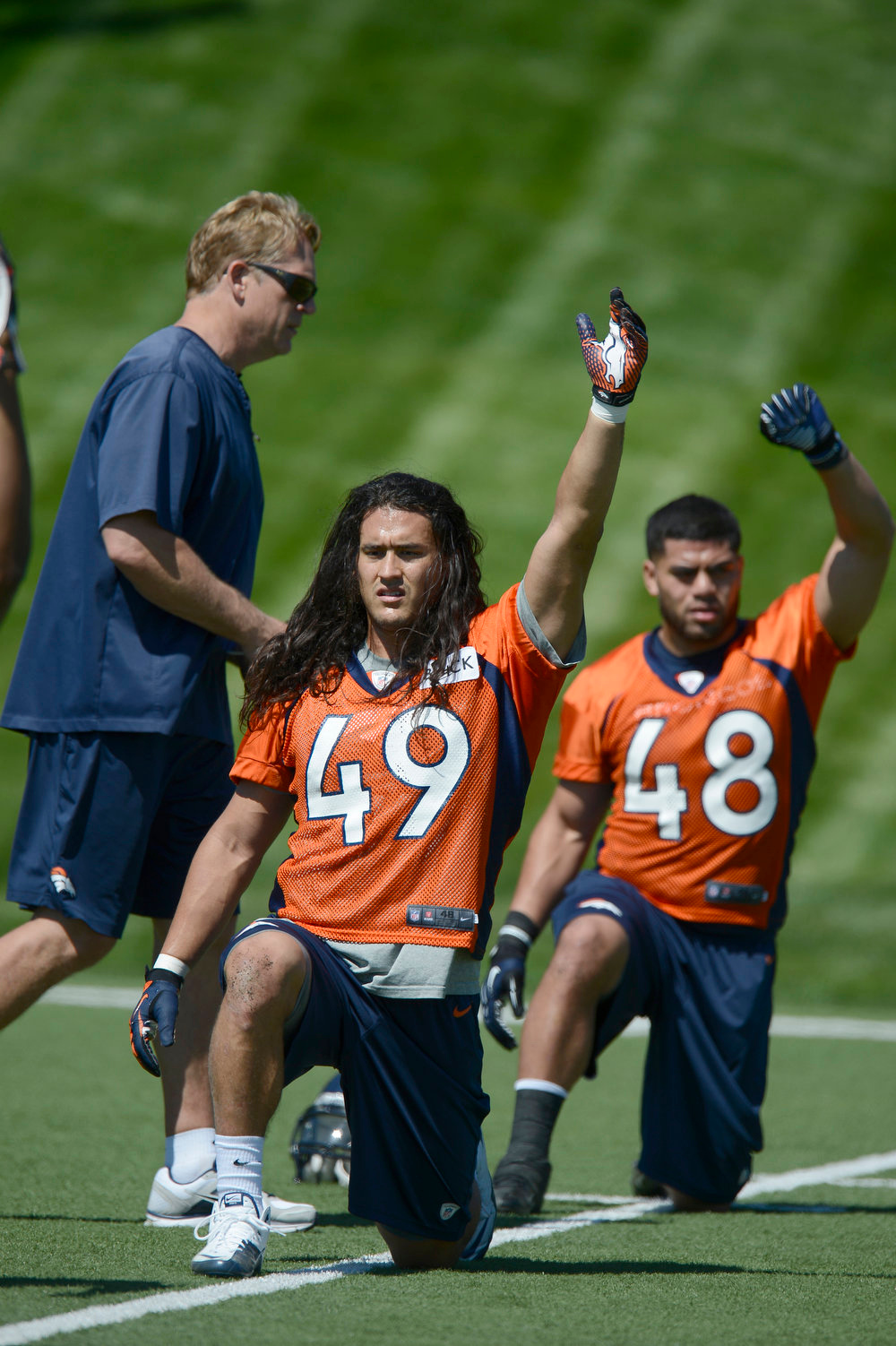 . Damien Holmes (49) of the Denver Broncos and Uona Kavelnga (48) stretch during last day of rookie mini camp May 12, 20313 at Dover Valley.   (Photo By John Leyba/The Denver Post)