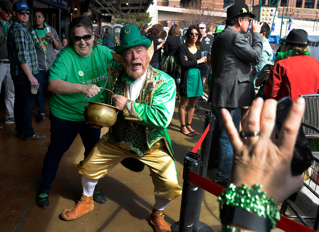 . Tammy Phillips, (right with phone camera) takes a photo of her sister Tina Brunz of Denver with Rocky the Leprechaun. It\'s Brunz\'s birthday. Everyone\'s Irish for the day at the Fado Irish Pub St. Patrick\'s Day celebration in downtown Denver on Tuesday, March 17, 2015. Rocky the Leprechaun was on hand taking photos with patrons along with Irish music and dance. (Photo by Kathryn Scott Osler/The Denver Post)