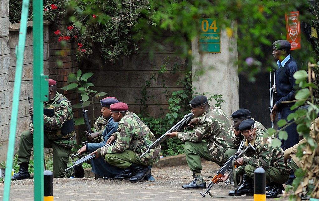 . Armed Kenyan policemen take cover outside the Westgate mall in Nairobi on September 23, 2013. AFP PHOTO / SIMON MAINA/AFP/Getty Images