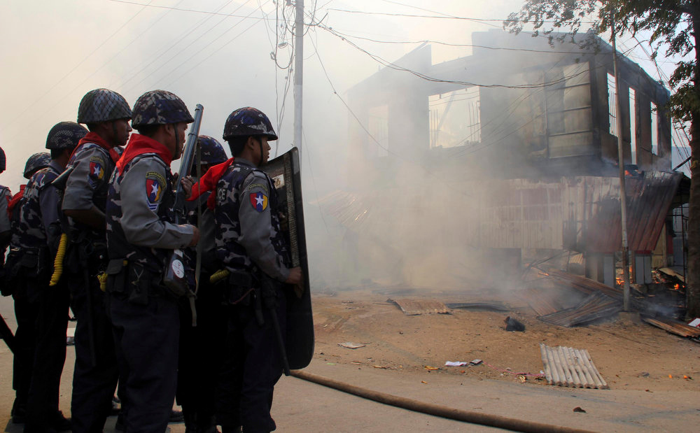 . Armed Myanmar police officers provide security around a smoldering building following ethnic unrest between Buddhists and Muslims in Meikhtila, Mandalay division, about 340 miles north of Yangon, Myanmar on March 21, 2013. Few imagined Myanmar would embrace democracy when the U.S. began its historic engagement with the military regime. The country\'s rapid changes were lauded by visiting Western leaders, and the nation\'s president was hailed as a hero. But spasms of spreading, communal violence show the reform path is bumpier that expected and have taken the sheen off a foreign policy success of the Obama administration\'s first term. (AP File Photo)
