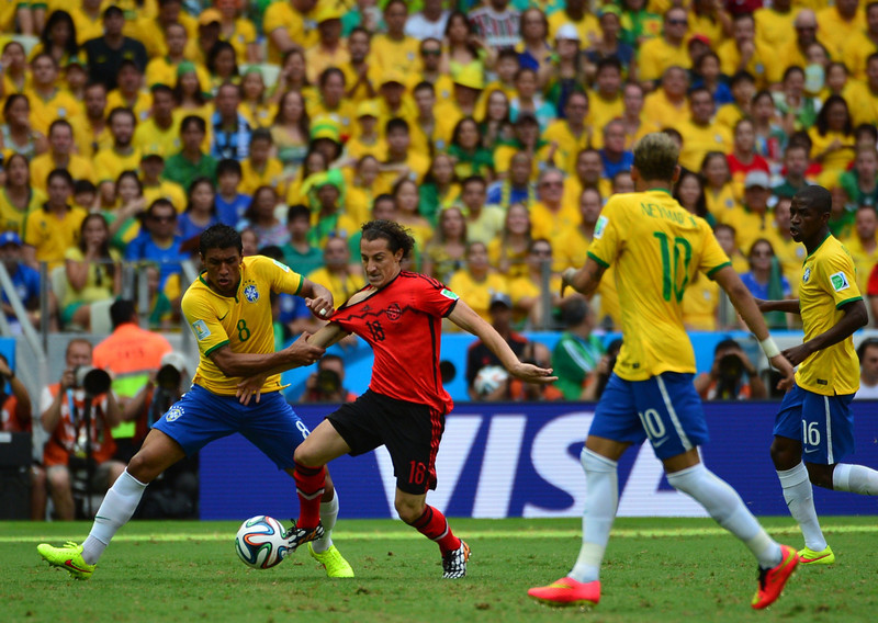 . Brazil\'s midfielder Paulinho (L) and Mexico\'s defender Andres Guardado vie for the ball during a Group A football match between Brazil and Mexico in the Castelao Stadium in Fortaleza during the 2014 FIFA World Cup on June 17, 2014.  (YURI CORTEZ/AFP/Getty Images)