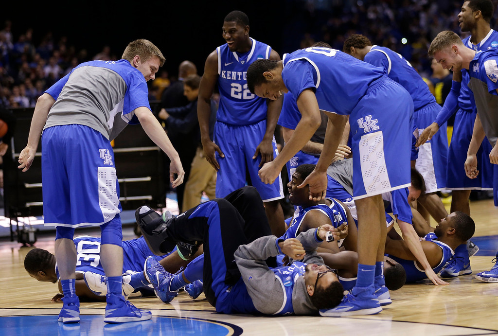 . Kentucky players celebrate after an NCAA Midwest Regional final college basketball tournament game against Michigan Sunday, March 30, 2014, in Indianapolis. Kentucky won 75-72 to advance to the Final Four. (AP Photo/David J. Phillip)