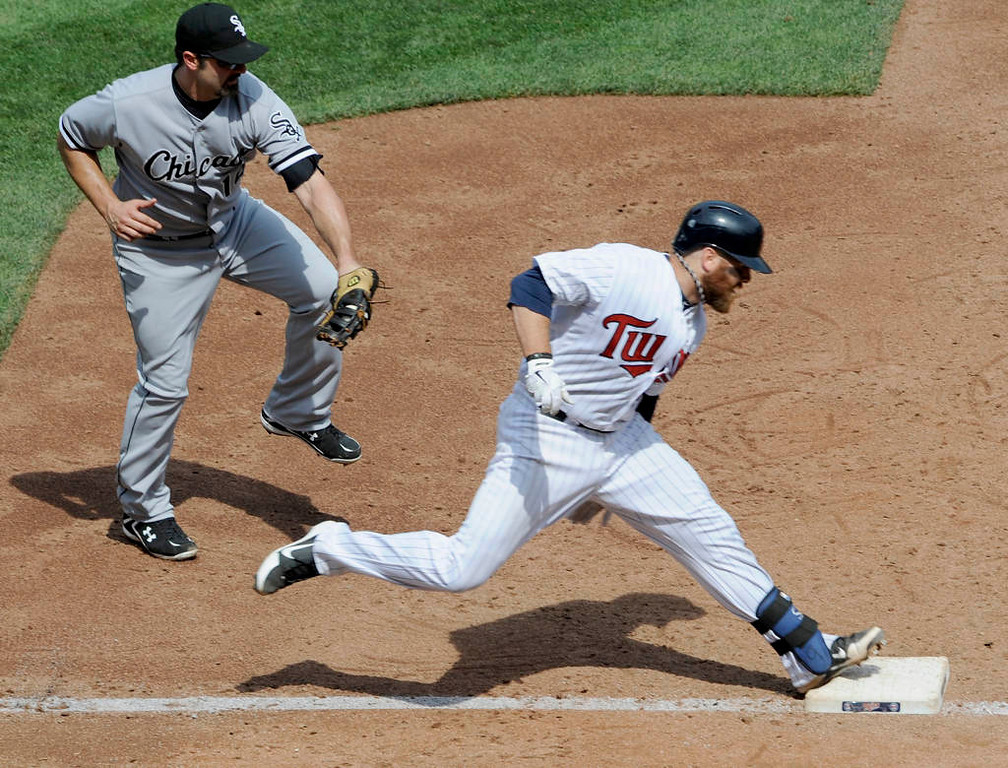 . Ryan Doumit of the Minnesota Twins avoids a tag by Paul Konerko  of the Chicago White Sox during the third inning. (Photo by Hannah Foslien/Getty Images)
