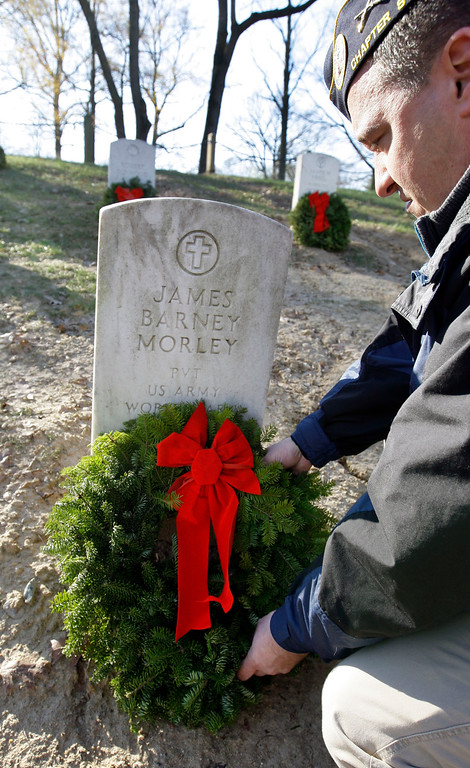 . Tim Howe of Warwick, R.I., a former Army staff sergeant now a member of the Disabled American Veterans Chapter 9, places a wreath as part of Wreaths Across America at Arlington National Cemetery in Arlington, Va., Saturday, Dec. 12, 2009. More than 16,000 wreaths were placed at graves throughout the cemetery. (AP Photo/Alex Brandon)