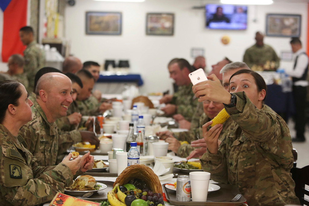 . A NATO soldier right, takes a selfie during the Thanksgiving meal at Resolute Support headquarters, in Kabul, Afghanistan, Thursday, Nov. 24, 2016. (AP Photo/Rahmat Gul)