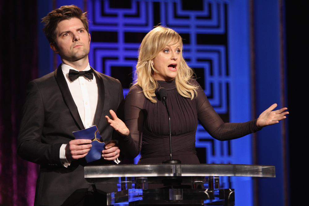 Description of . Actors Adam Scott and Amy Poehler speak onstage at the 2013 WGAw Writers Guild Awards at JW Marriott Los Angeles at L.A. LIVE on February 17, 2013 in Los Angeles, California.  (Photo by Maury Phillips/Getty Images for WGAw)